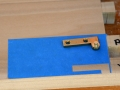 Cutting hinge mortise shape in blue tape improves visibility when routing